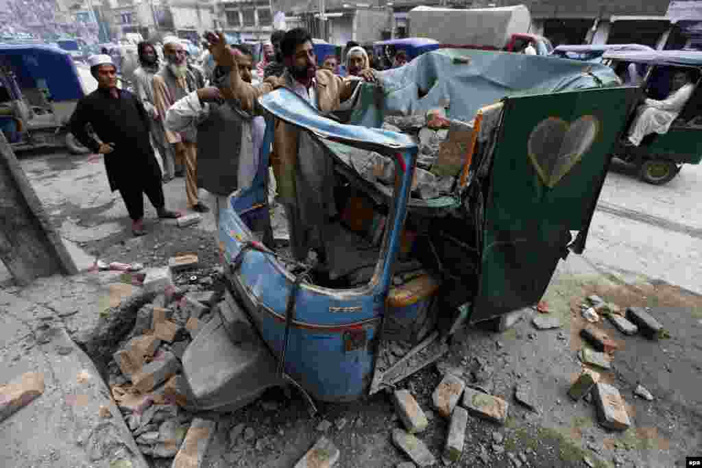 People remove debris from a rickshaw in Peshawar, Pakistan.