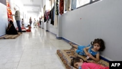 Syrian children, whose families have fled clashes between rebels and regime forces in Damascus and Homs, lie on a mattress at a school where refugees have taken shelter in the neighborhood of Mazzeh.