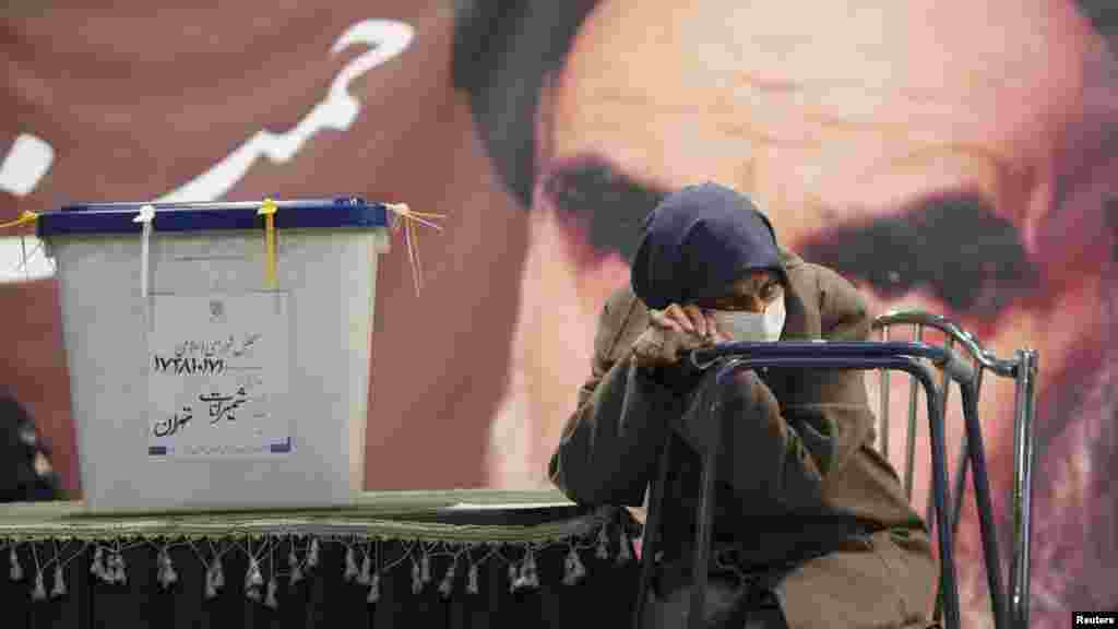 A sick woman waits beside a ballot box in Tehran as election officials register her to vote in Iran's March 2 parliamentary elections. (Reuters/Stringer)