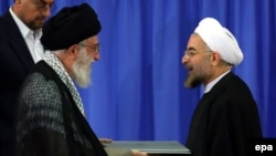 Iranian Supreme Leader Ayatollah Ali Khamenei (left) gives an endorsement letter to newly elected President Hassan Rohani during a ceremony for his confirmation as Iran's president in Tehran on August 3.