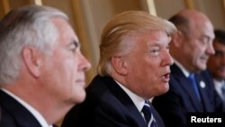 U.S. President Donald Trump talks beside Secretary of State Rex Tillerson. File photo