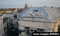 A reclining rooftop character stands opposite St. Stephen's Basilica.
