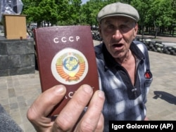 Чоловік демонструє паспорт, на обкладинці якого напис СРСР і колишній радянський герб. Луганськ, 10 травня 2014 року