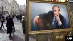 Люди проходят мимо портрета президента России Владимира Путина на улице Арбат. Москва, 12 марта 2004 года.