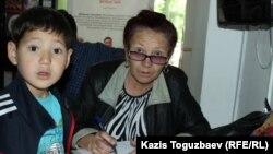 Жительница Капшагая Алматинской области Куляш Умирова – мать подсудимой Жанны Умировой, обвиняемой в пропаганде терроризма, – с внуком (сыном дочери Жанны) Ахматом в фойе Алмалинского районного суда. Алматы, 7 июня 2017 года.