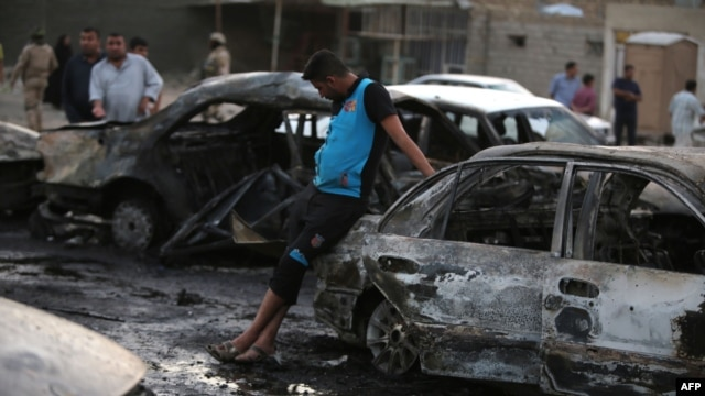 Iraqi men gather at the scene of one of two car bombs that exploded in Baghdad's Habibiyah neighborhood on May 27.