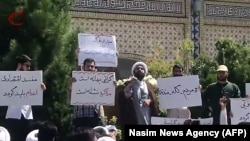 An Iranian cleric speaks to a crowd of protesters demonstrating in the city of Mashhad, in the Khorasan Razavi province, on August 3.
