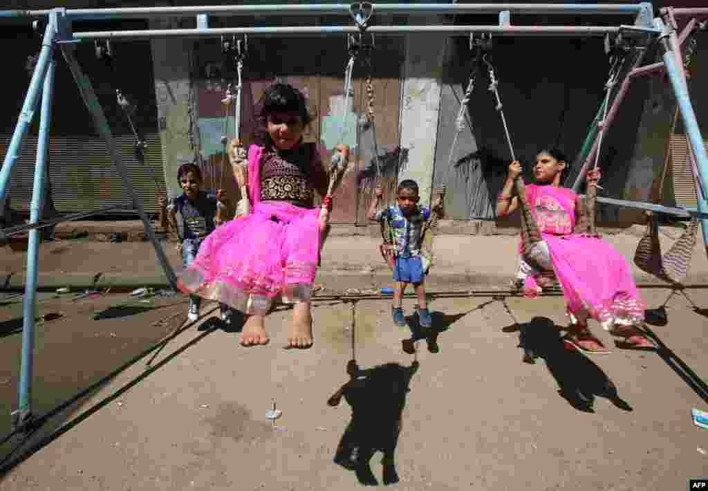 Iraqi children play on a street in the capital, Baghdad, on the first day of the Eid al-Adha holiday. (AFP/Ahmad al-Rubaye)