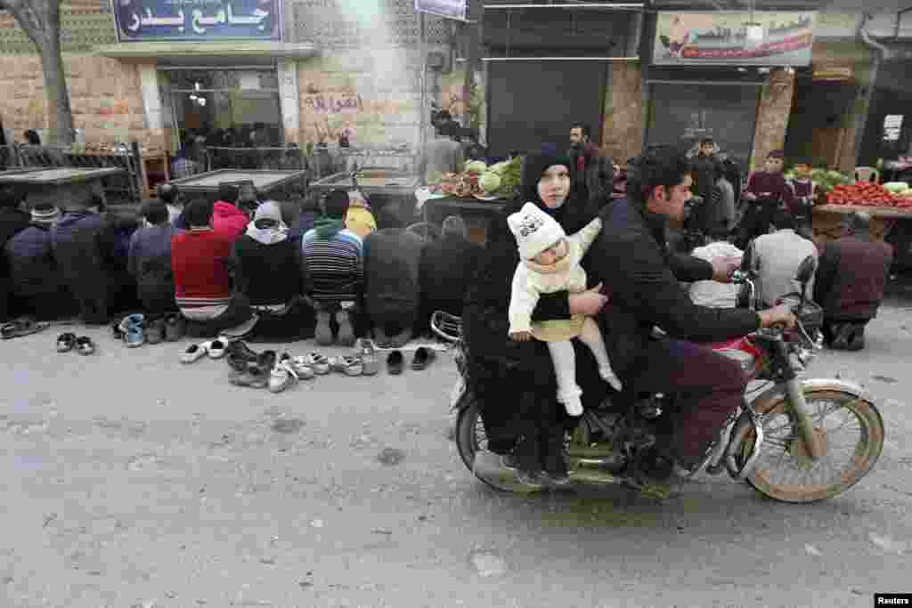 A couple with a child ride a motorcycle past demonstrators praying along a street, before a protest against Syrian President Bashar al-Assad in the Bustan al-Qasr district in Aleppo. (Reuters/Muzaffar Salman)
