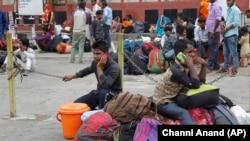 Готовящиеся покинуть штат Джамму и Кашмир индийские трудовые мигранты разговаривают по телефону на железнодорожном вокзале. 7 августа 2019 года.