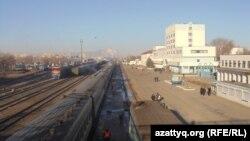 Железнодорожный вокзал в Актобе на фоне дымящих труб городских промышленных предприятий.