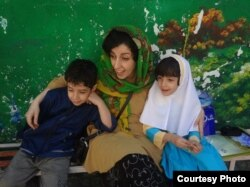 Iran -- Iranian human rights activist, Narges Mohammadi (C), with her children, Ali (L) and Kiana, undated.