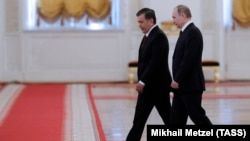 Uzbek President Shavkat Mirziyaev (left) and Russian President Vladimir Putin on their way to a meeting at the Kremlin in Moscow on April 5.