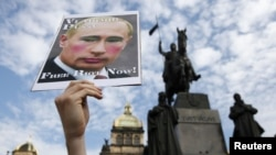 Czech Republic -- An activist holds a poster depicting Russian President Vladimir Putin in support of members of the female punk band Pussy Riot during a protest rally at Wenceslas Square in Prague. August 17, 2012.