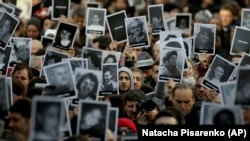 People hold up pictures of those who died in the AMIA Jewish center bombing that killed 85 people as they commemorate the attack's 22nd anniversary in Buenos Aires, Argentina, Monday, July 18, 2016. File photo