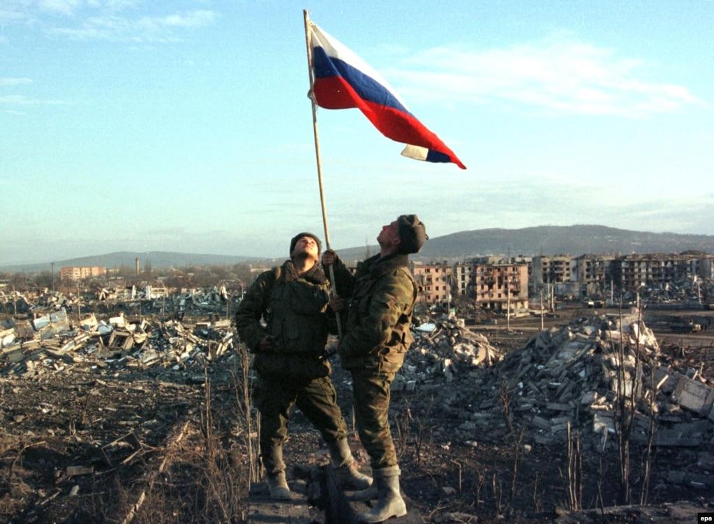 Әскерилер Грозныйда Ресей туын ұстап тұр. 2000 жылдың ақпаны. Бұл уақытта Ресей Грозныйды алған еді.