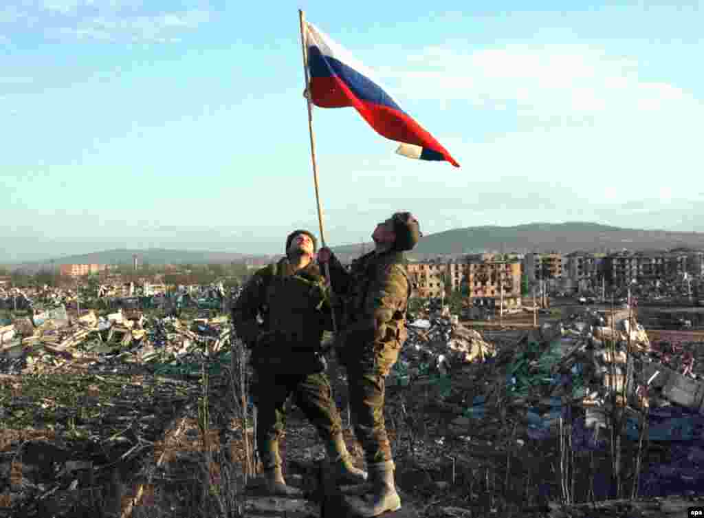 Troops raise a Russian flag in the center of Grozny in February 2000. By the time federal forces recaptured the city, much of it had been reduced to ruins by Russian bombs and by other weapons in the fighting.