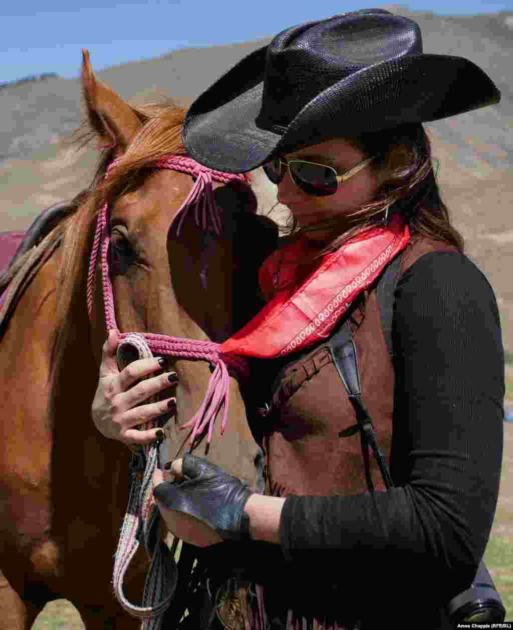 "Texan Susannah Winfield comforts her horse before the event. Winfield told RFE/RL there was some head scratching among the U.S. contingent over what exactly America's traditional dress was: ""I think a lot of [Kyrgyz] people thought we would compete in native American clothing, but we had to explain that we can't really do that, and we figured the cowboy look would be less controversial."""