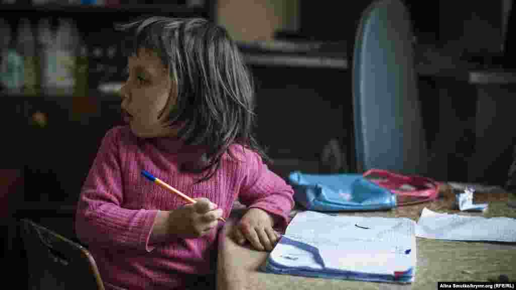 Нурие рисует в своей тетради