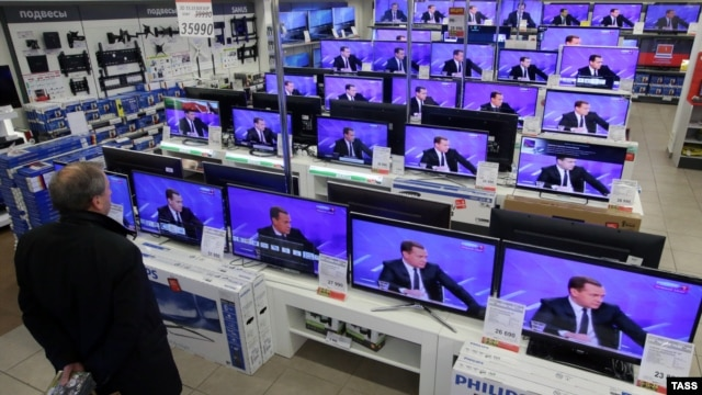 A man looks at televisions in a Moscow showroom as Russian Prime Minister Dmitry Medvedev answers questions in December.