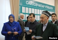 People wait to vote at a polling station in Tashkent on December 4.