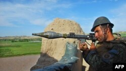 FILE: An Afghan National Army soldier handles a rocket-propelled grenade launcher as he keeps watch during a patrol in Bala Murghab district of northwestern province of Badghis.