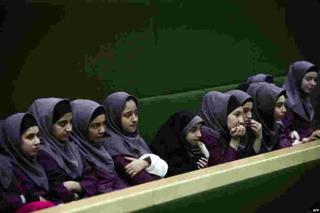 Iranian schoolgirls observe members of parliament discussing a draft bill that would limit photographers' access to cover parliament's open sessions in Tehran. (AFP/Behrouz Mehri)