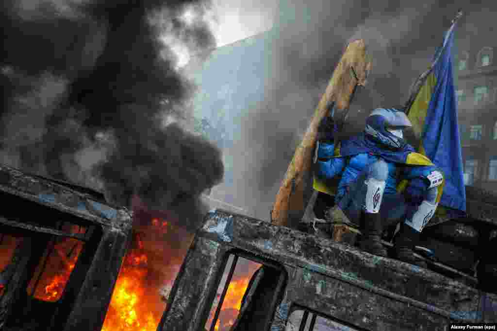 A protester protects himself from a fire as he sits on the roof of a burned-out bus in downtown Kyiv.