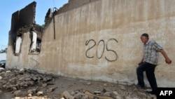 Ұлтаралық жанжал кезінде түк қалмай өртеніп кеткен үйінің орнында жүрген тұрғын. Ош қаласы, Қырғызстан, 14 маусым 2010 жыл.