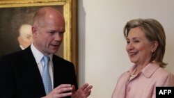U.S. Secretary of State Hillary Clinton and British Foreign Minister William Hague chat in Washington.