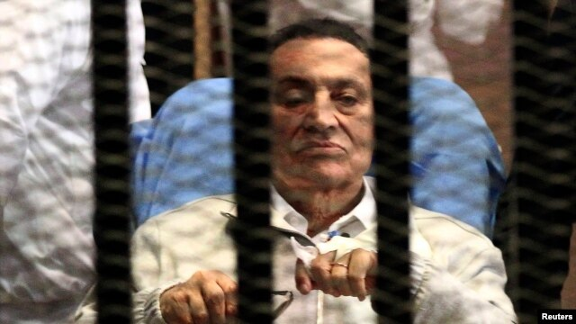Former President Hosni Mubarak sits inside a dock at the police academy on the outskirts of Cairo in April.