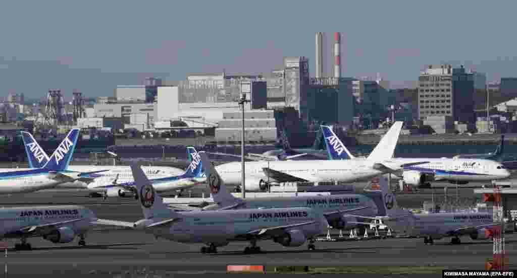A view of Japan Airlines (JAL) and All Nippon Airways (ANA) airliners parked on the tarmac at Tokyo International Airport on April 14.