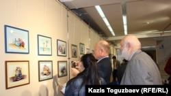 Посетители выставки карикатур, посвященной Всемирному дню свободы прессы. Алматы, 30 апреля 2015 года.