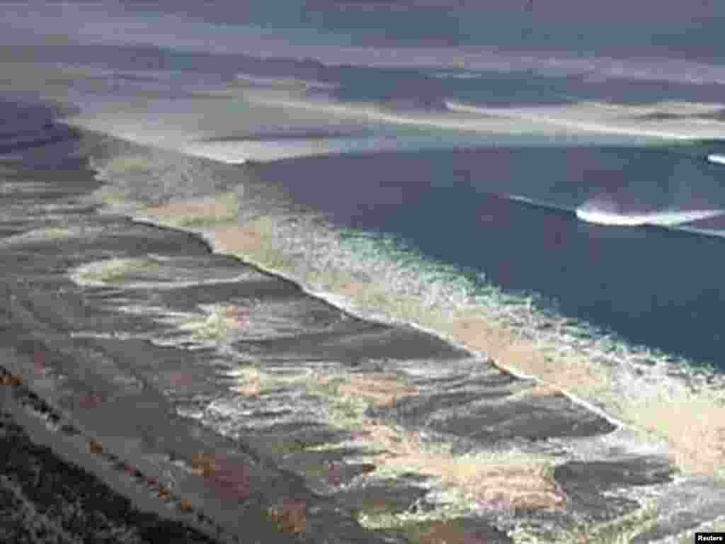 Japan -- Tsunami waters engulf Sendai in this still image taken from video footage, 11Mar2011 - Цунами в Сендае. Скриншот 11 марта 2011. REUTERS/NHK via Reuters TV