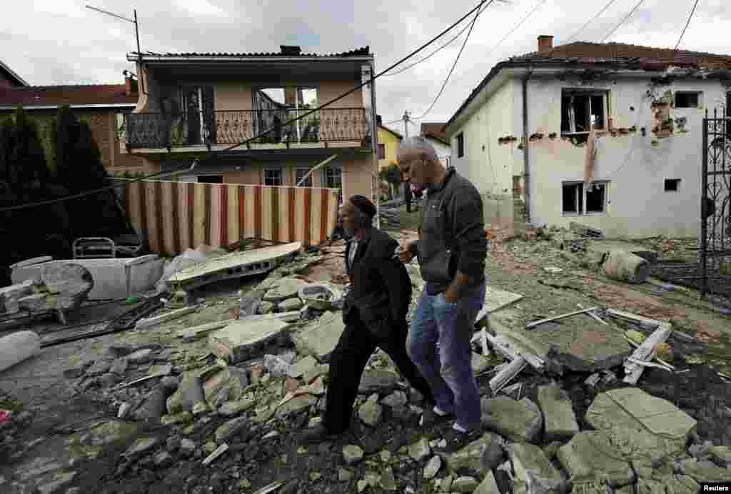 People walk past houses damaged in the gunbattle in Kumanovo.