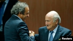 Switzerland -- UEFA President Michel Platini (L) congratulates FIFA President Sepp Blatter after he was re-elected at the 65th FIFA Congress in Zurich, Switzerland, May 29, 2015.