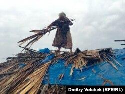 Старушка обновляет крышу своей хижины после дождя