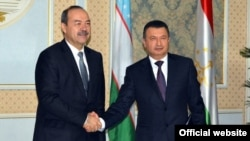 Takjik Prime Minister Qohir Rasulzoda (right) welcomes Uzbek counterpart Abdullo Aripov to Dushanbe on January 11.