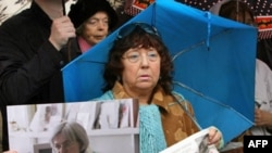 A woman holds pictures of Politkovskaya in Moscow on October 7, the second anniversary of her murder.