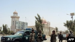 Afghan security forces stand guard in front of the mosque in Kandahar on July 14.