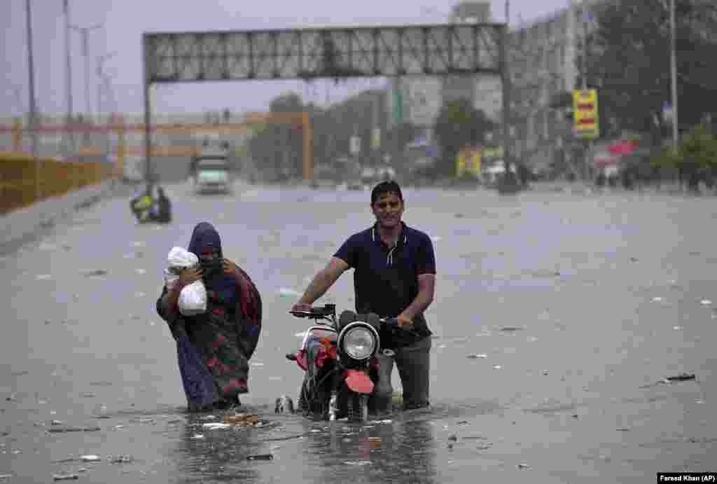 A family wades through a flooded road after torrential rain in Karachi, Pakistan. (AP/Fareed Khan)