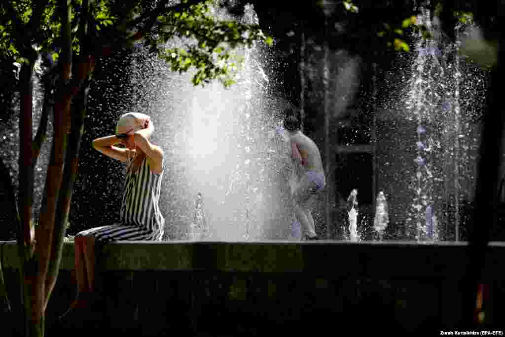A woman listens to music as she sits on the edge of a public fountain while a child plays nearby amid scorching midday heat in Tbilisi. Temperatures reportedly reached up to 38 degrees Celsius in the Georgian capital. (epa-EFE/Zurab Kurtsikidze)
