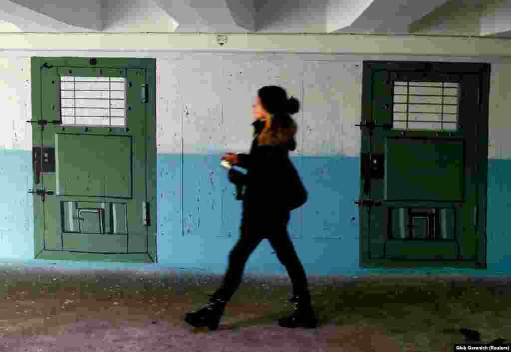 Девушка идет по подземному переходу, разрисованному под тюремный коридор в центре Киева. (Reuters / Глеб Гаранич)