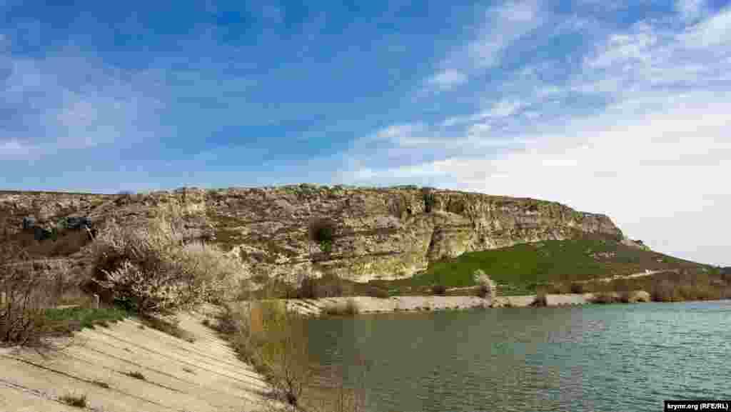 Вид на Волчий грот (слева от цветущей алычи) с дамбы водохранилища на реке Бештерек