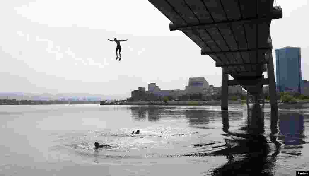 A boy jumps into the Yenisei River from a foot bridge in the Siberian city of Krasnoyarsk, Russia. (Reuters/Ilya Naymushin)