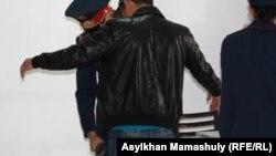 Полицейский проверяет молодого мужчину в здании, где проходит суд по событиям Шетпе. Актау, 23 апреля 2012 года.