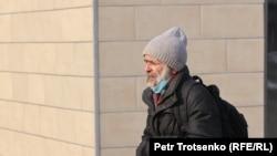 Коронавирус індеті кезінде көшеде маска тағып кетіп бара жатқан ер кісі. Алматы, 4 қаңтар 2021 жыл.