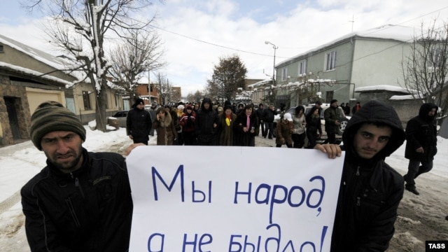 "Dzhioyeva supporters hold up a sign saying, ""We are people, not sheep."""