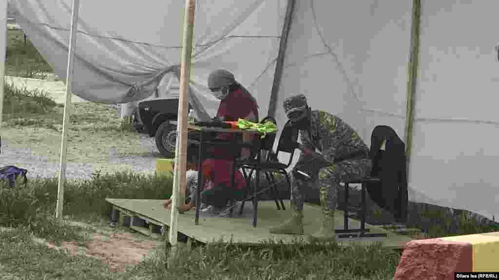 Мақтаарал ауданындағы блокпостта отырған балалы әйел мен әскери адам.
