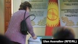 Женщина у электронной урны. Бишкек, 4 октября 2015 года.